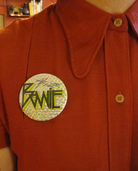 Addicted to brooches and badges : orange arrow brooch , vintage spool of thread brooch , vintage Buzzcocks badge and  vintage Bowie pinback button .   1950 1960 1970 50s 60s 70s pin button punk david bowie ziggy stardust