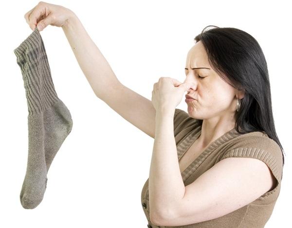 mulher segurando meia com chulé
