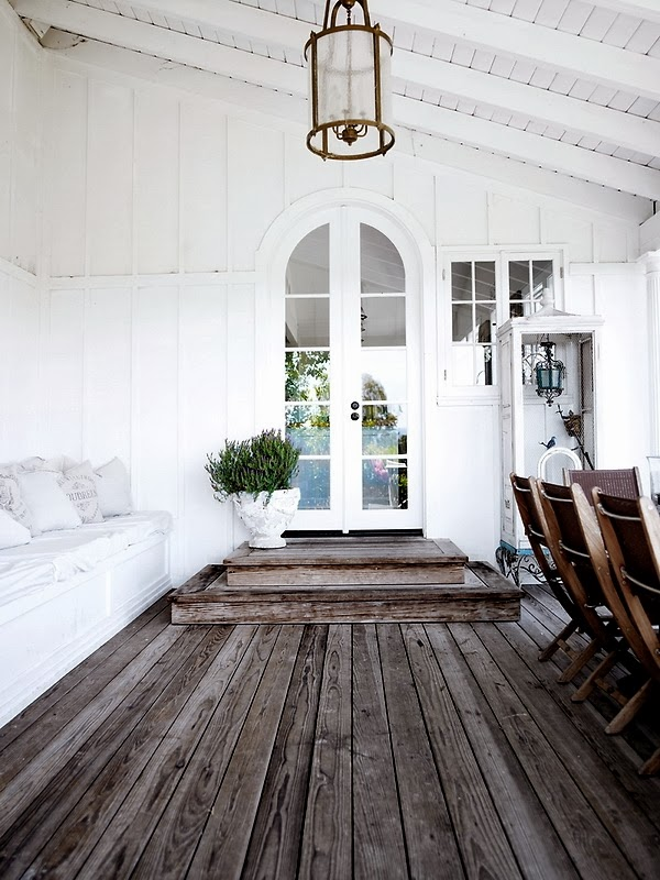 White arched doorway from a covered patio into a home with grey deck flooring and built in bench seating