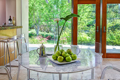 reflective dining table and transparent dining chairs with a fresh green centerpiece in a bright room scheme