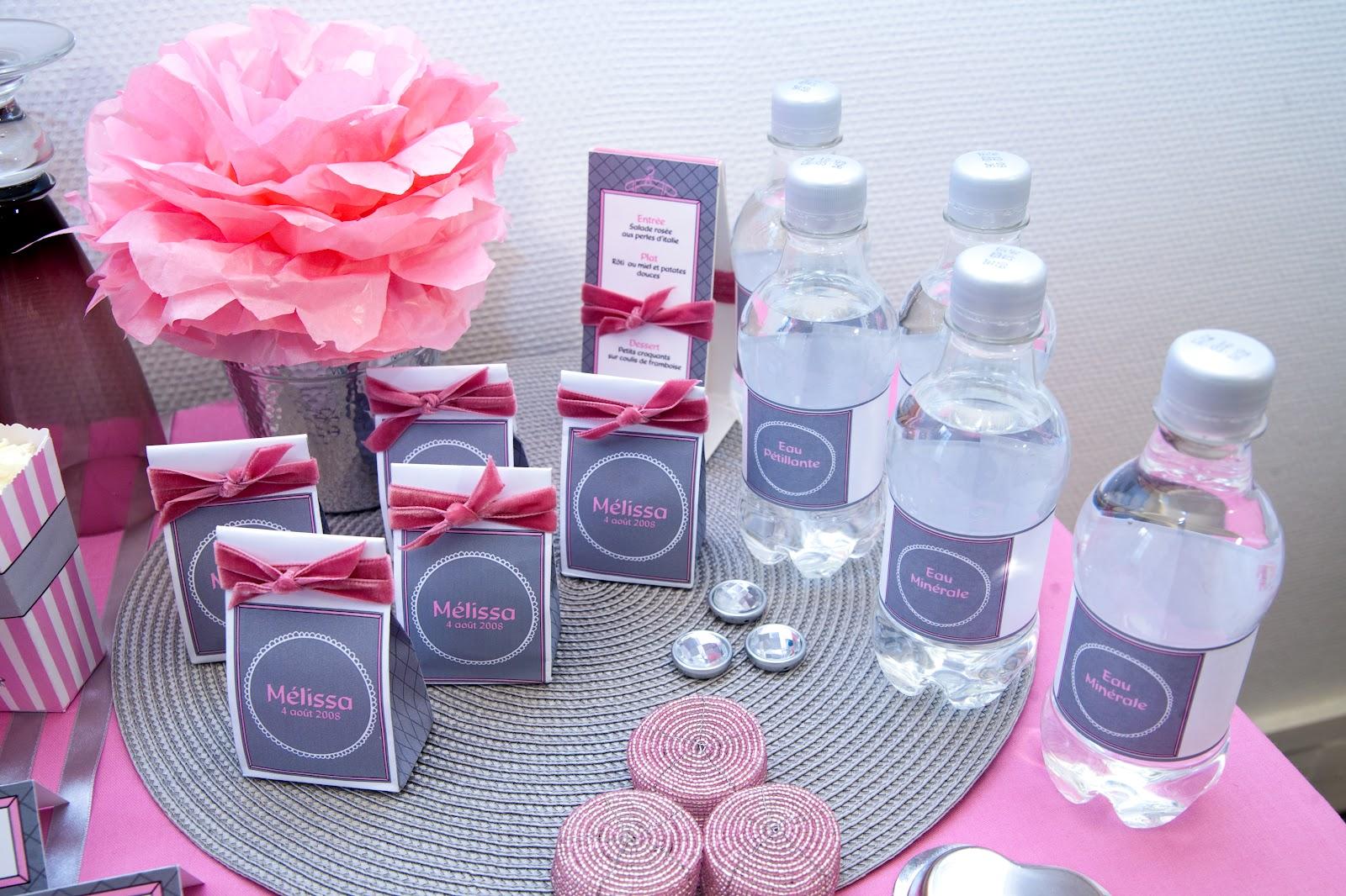 Pompom rose sur nappe rose avec set de table gris, bouteille d'eau et cadeau invité