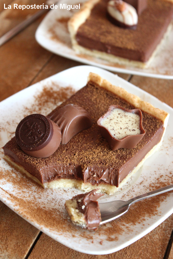Porción central de la tarta con tres bombones, vista en un primer plano. De fondo difuminado se aprecia parte de otra porción, realmente el aspecto es irresistible para los amantes al chocolate.Le falta un par de cucharadas, apreciando la cremosidad del relleno.