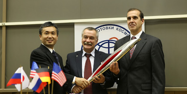 At the Gagarin Cosmonaut Training Center in Star City, Russia, Expedition 38 Flight Engineer Koichi Wakata of the Japan Aerospace Exploration Agency (left), Soyuz Commander Mikhail Tyurin (center) and NASA Flight Engineer Rick Mastracchio pose for pictures with a model of the Olympic torch following a crew news conference Oct. 22, 2013. The trio is scheduled to launch Nov. 7, Kazakh time, from the Baikonur Cosmodrome in Kazakhstan on the Soyuz TMA-11M spacecraft for the start of a six-month mission on the International Space Station. Launching with the the crew will be one of the Olympic torches used in the Olympic relay that will culminate with the torch's arrival at the opening ceremonies of the 2014 Winter Olympics in Sochi, Russia next February. Photo credit: NASA