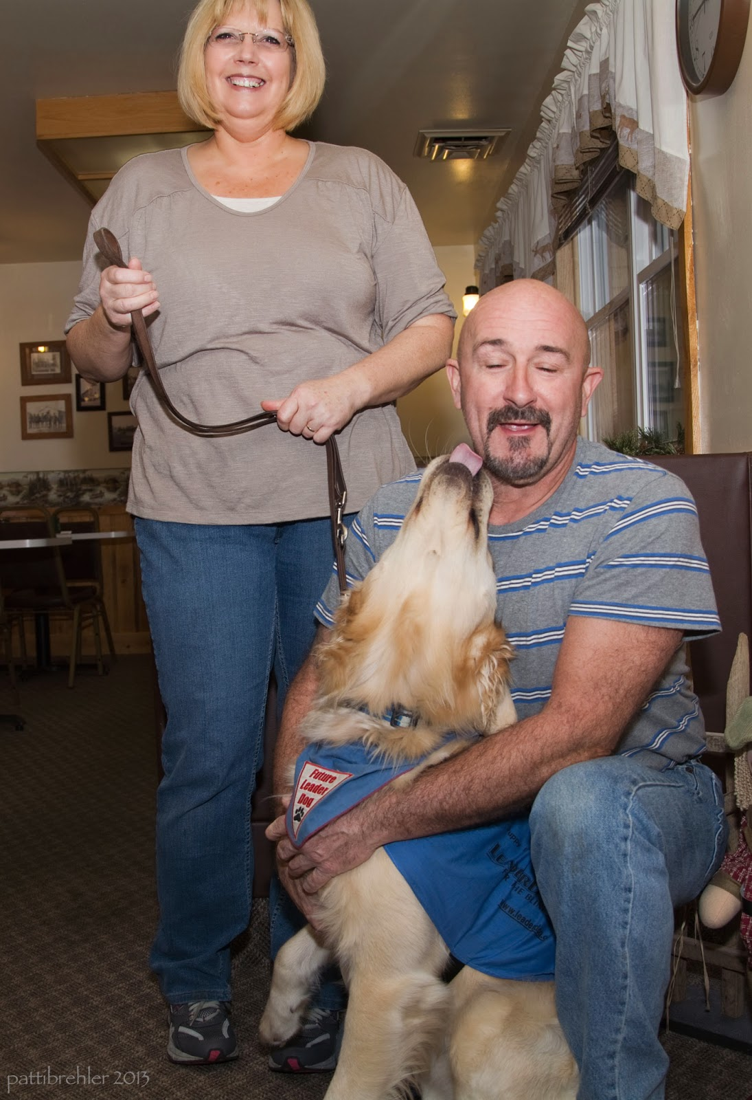 A woman with short blond hair wearing a grey short-sleeved shirt and blue jeans is standing on the left holding a brown leash. A bald man with a goatee and mustache is kneeling on one knee on the right. He is trying to hold a golden retriever, who is trying to lick the man's face. The man has his eyes closed and the woman is smiling. The man is wearing a gray and blue striped short sleeved shirt and blue jeans. The dog is wearing a blue jacket and a blue bandana.