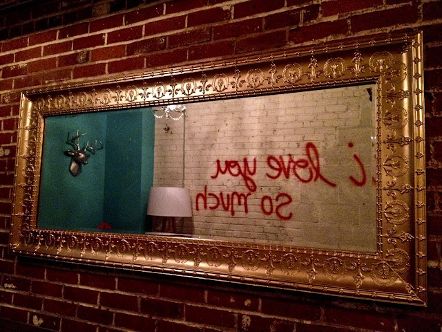 "Graffiti at Punch Bowl Social in Denver viewed in a mirror that says, ""I love you so much""."