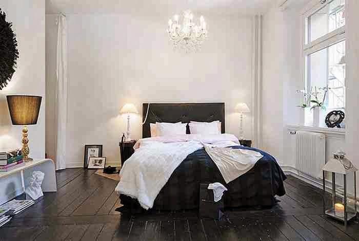 Biała sypialnia z czarną podłogą, czarne deski na podłdze i dodatki glamour, czarny zagłówek nad łóżkiem