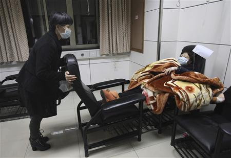 A patient with fever (R) is accompanied by a family member while receiving treatment at the hospital where a 67-year-old H7N9 patient is being treated, in Hangzhou, Zhejiang province, April 3, 2013. REUTERS/Chance Chan