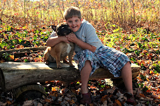 boy with Down syndrome hugging a french bulldog in the fall landscape