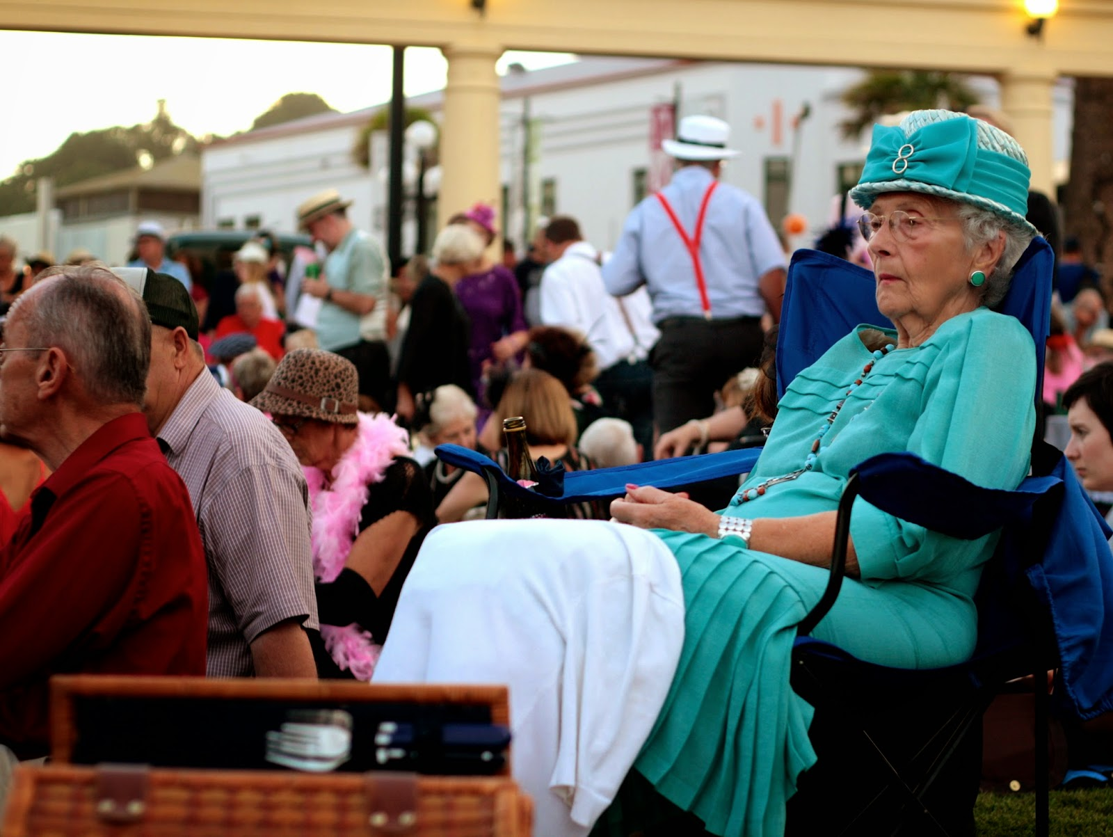 An older woman wears a mint green dress and matching hat.