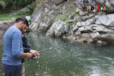 Divyam learning how to operate a fishing rod
