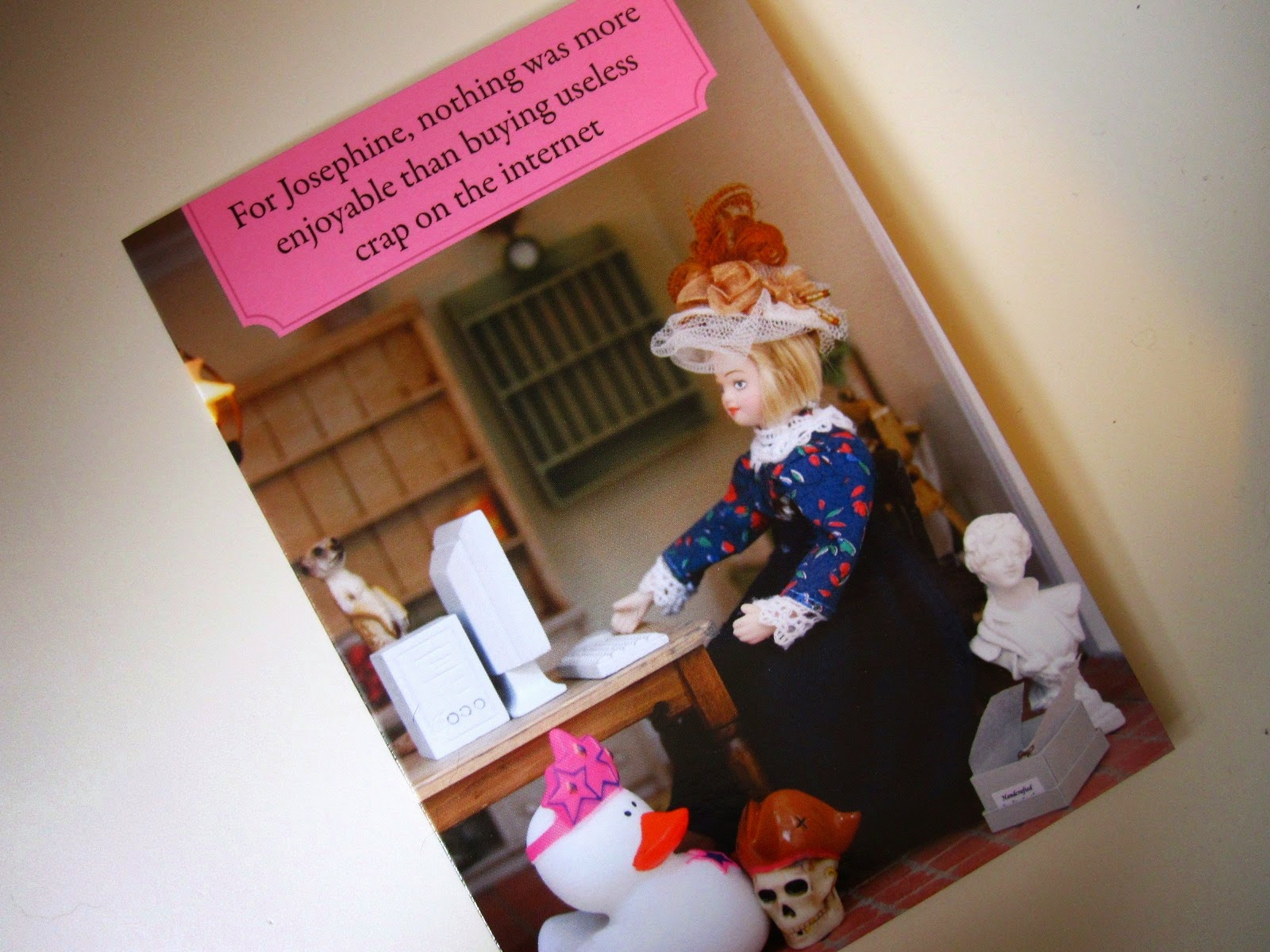 Greeting card showing a dolls house doll at a miniature computer, surrounded by random items. Card reads 'For Josephine, nothing was more enjoyable that buying useless crap on the internet'.