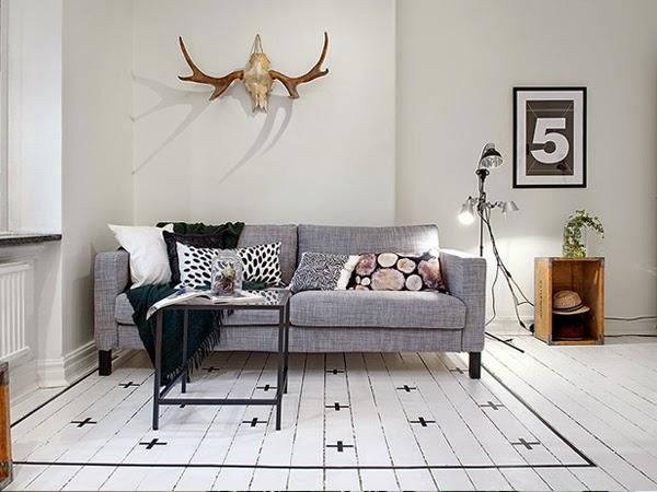Sofa w salonie i nad nią poroże