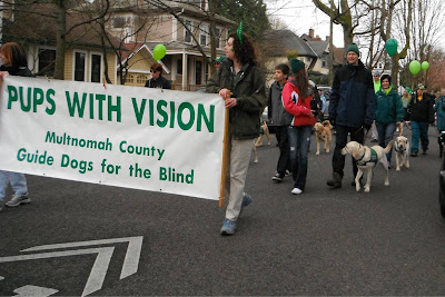 raisers carry a banner titled Pups with Vision, following behind them march more raisers and their puppies