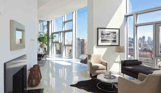 Den with encasement windows with amazing views of NYC, a fireplace, brown bench seating, cream armchairs and a round coffee table.