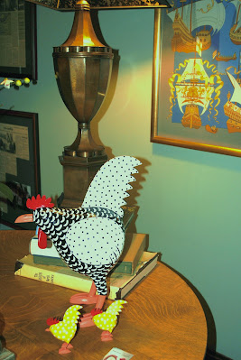 a black and white spotted chicken folk art peice sitting on a table with lamp and framed picture with ships in backgroungd