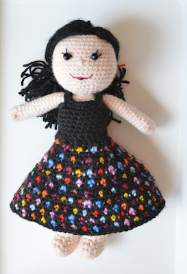 Kwokkie Doll in an outfit of 'Dotty Daywear': a black sleeveless top and a black skirt covered in brightly-coloured polka-dots.