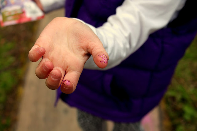 girl holding out hand covered in pink glitter