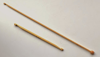 Two bamboo hooks photographed on the diagonal: (lower left) 6 mm diameter double-ended hook 15 cm long; (top right) 4 mm diameter tricot (Tunisian) hook 30 cm long. The head of the hook is at the top left and the stop is on the bottom right end.
