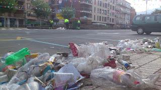 Grandes cantiadades de basura en primer plano, al fondo los empleados del servicio de limpieza