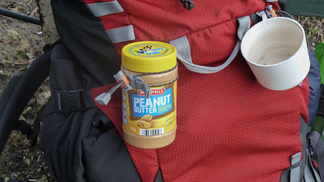 jar of peanut butter on outside of backpack