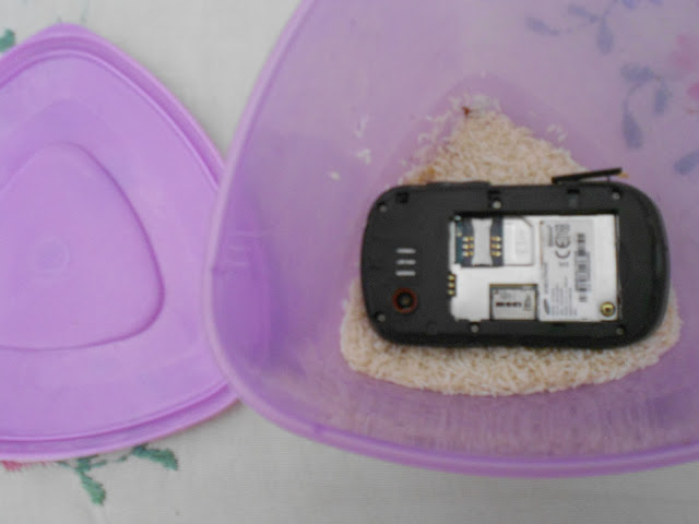 Mobile phone in a container with dry rice