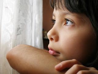 niño triste mirando a través de la ventana