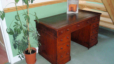 A photograph of a restored pedestal desk, including a new leather