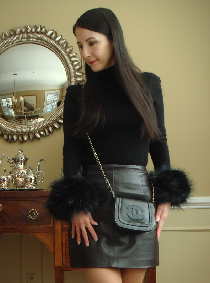 Black faux fur cuffs on the sleeves of a black turtleneck with a leather skirt and black crossbody.