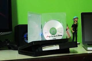 Foto de uma fita cassete comum junto a um DVD