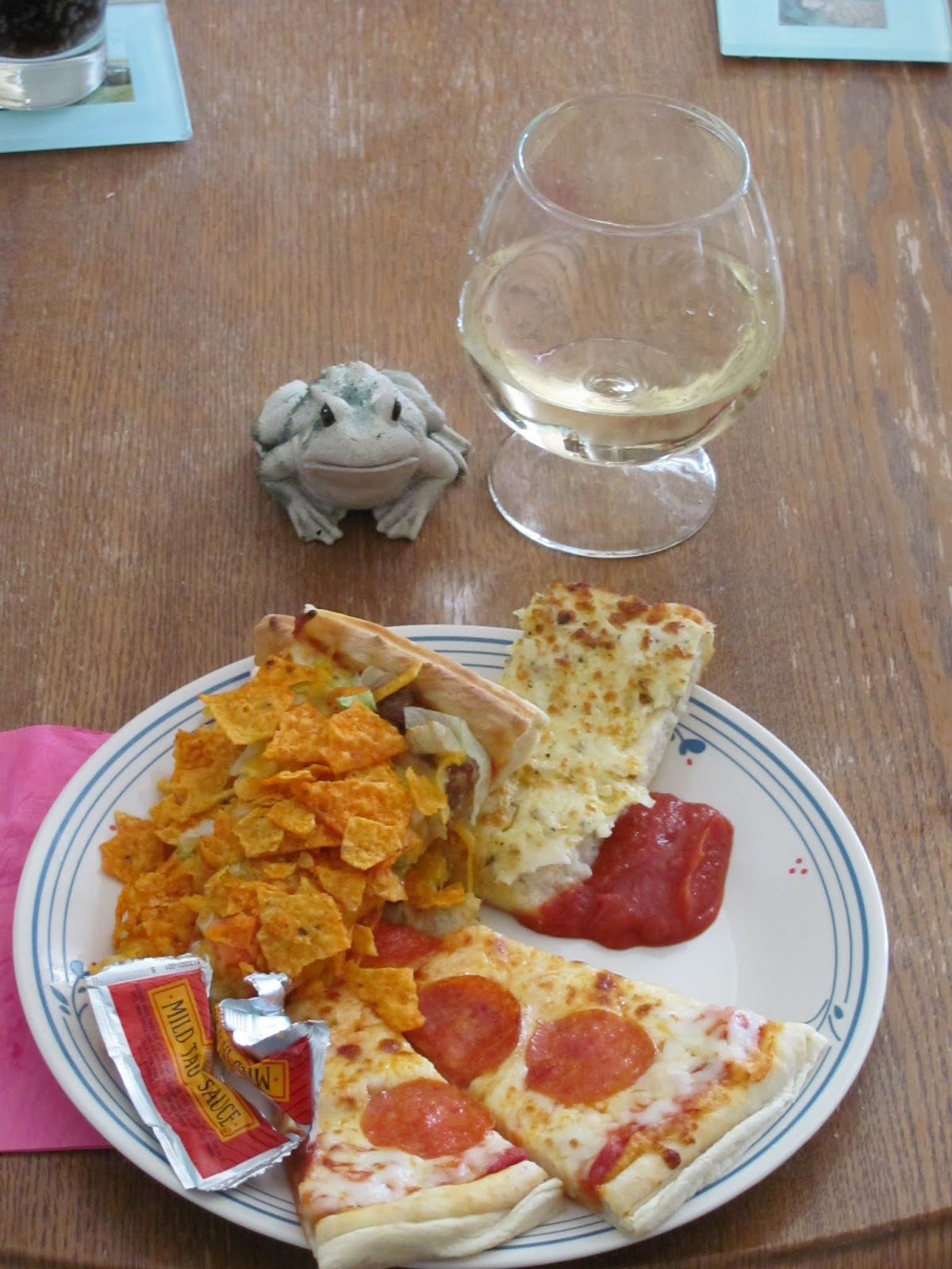 Frog poses with a plate of pizza and white wine in Coralville, Iowa