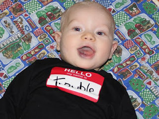 "High Need Baby wearing shirt that says ""Hello my name is Trouble"""