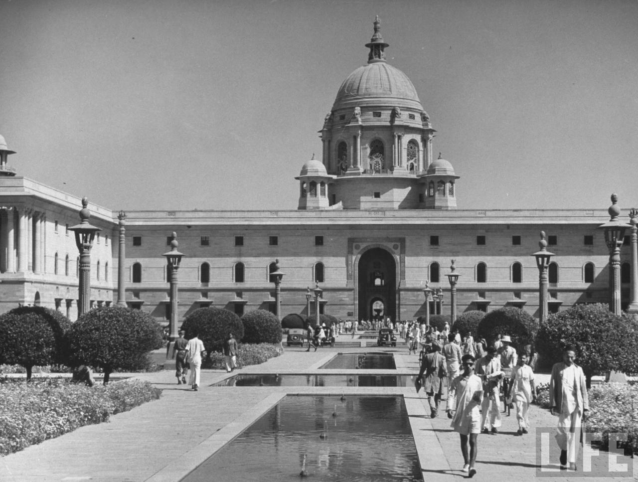 Indian government workers walking along mall in front Indian building photos