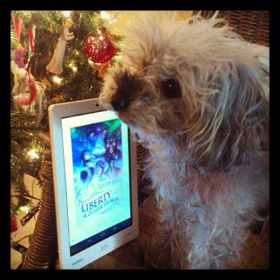 Murchie stands on a wicker chair, his chin upraised and his attention focused off panel. Beside him sits my Kobo with the Liberty and Other Stories' cover art on its screen. The cover features four people of a variety of races, all bathed in a purple glow. Behind the Kobo is a Christmas tree.