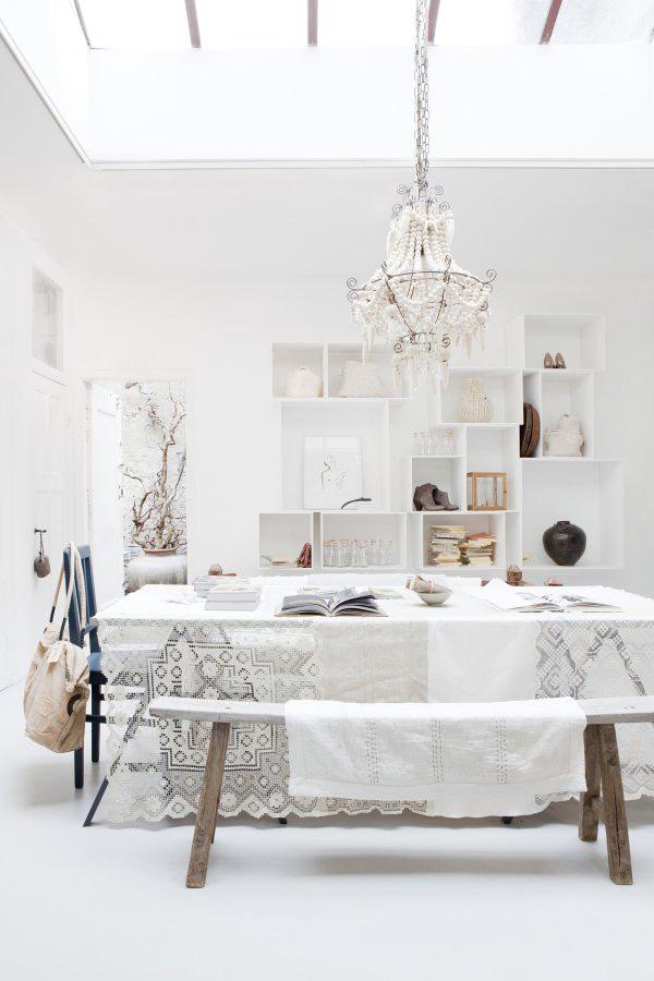 mesa con mantel de encaje y banco de madera rustica