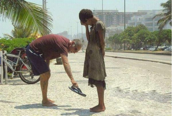 Picture of a man giving his shoes homeless in Rio de Janeiro. The girl began to cry.