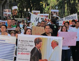 Manifestação em Curitiba (PR) contra a aprovação do PLC 3/2013 (a nova lei do aborto no Brasil. No 1º cartaz os dizeres: A mesma mão que apertou a mão do Papa assinou Projeto  favorecendo o aborto!