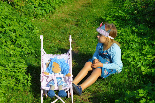 Girl sits next to doll in pushchair