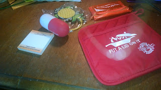 L-R Posti-t pad, foam capsule stress reliver, pineapple luggage tag, plastic card case and awesome potholder