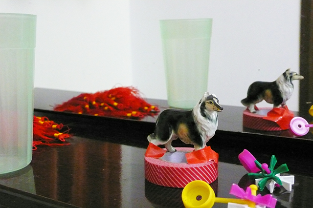 Ceramic dog attached to a roll of red tape on a shelf by a mirror.