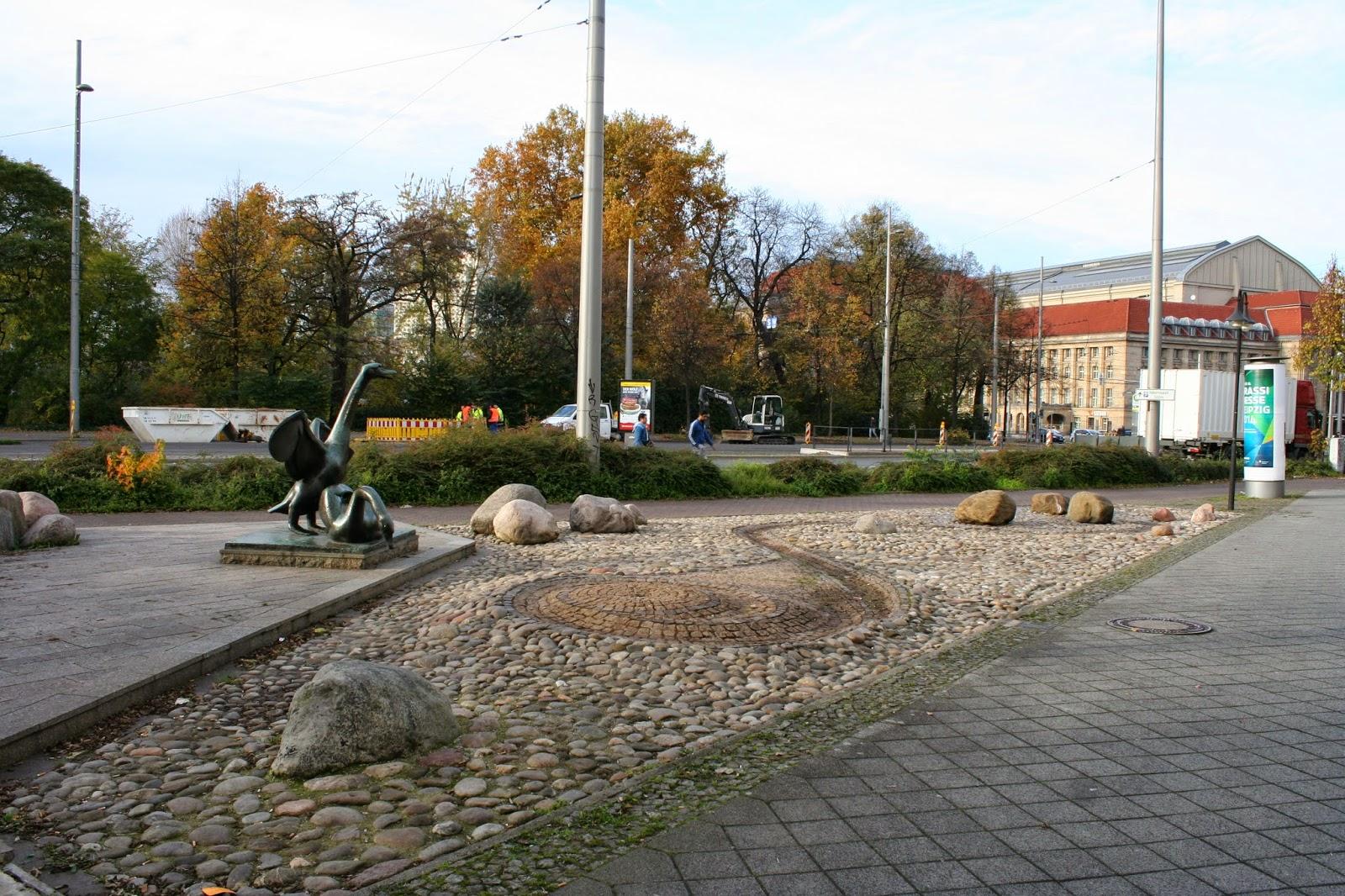 Schwanenbrunnen ohne Wasser - im Hintergrund der Hauptbahnhof