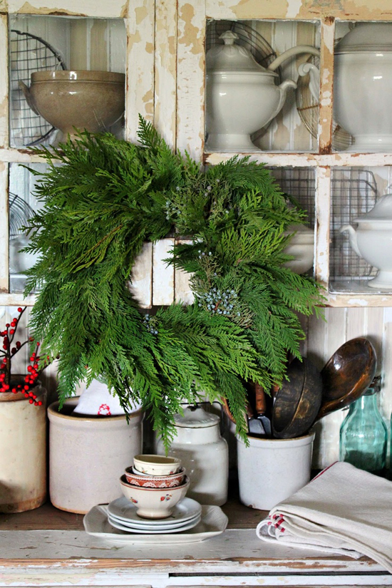 Small evergreen wreath hung in front of vintage cabinetry in the kitchen of Rusty Hinge
