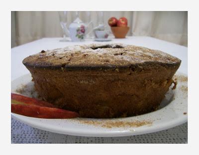 Na parte inferior da imagem, vê-se parte de uma toalha de mesa de crochet filet branco, por baixo de um prato branco redondo. No centro da imagem, em cima do prato branco, um bolo marrom de furo redondo centralizado. Ao fundo são vistos desfocados, o restante da toalha de mesa, um bule, três xícaras e pires de porcelana branca decorada com flores, quatro taças de vidro transparente, pequena tigela de barro marrom com três maças vermelhas, e parte de uma cortina de tecido bege.