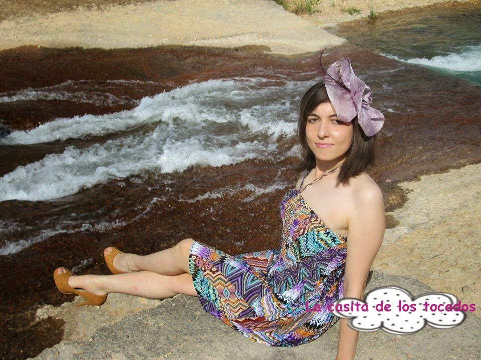 tocado de sinamay malva combinado con vestido corto estampado