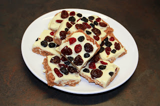 Image of flaphack covered in white chocolate with dried blueberries, cranberries and sour cherries