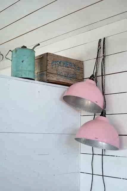 Metalowe klosze lamp i pastelowy róż, pastelowa metalowa konewka, białe wnętrze