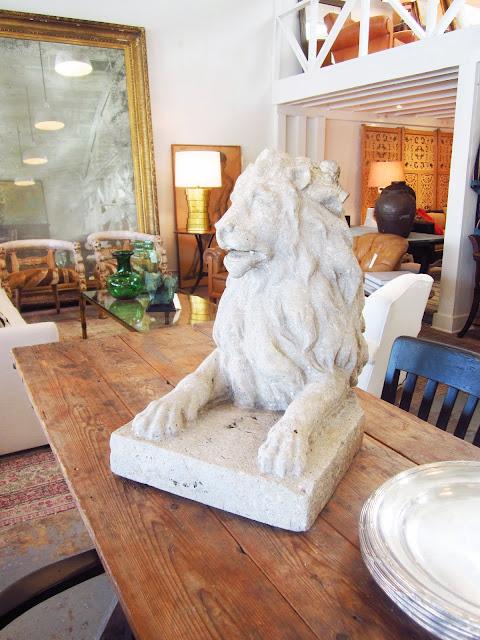 stone lion statute on a wood table inside Brenda Antin