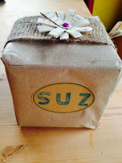 Handmade gift wrapping using brown paper and crafted paper flower