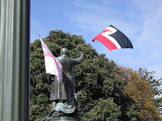 A statue of Richard Seddon with a Tino Rangatiratanga flag and a flag of the United Tribes
