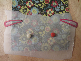 two hairclips and two magnets secure the greaseproof paper to the patterned paper