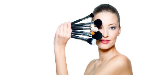 Modelo exibe pincéis de maquiagem.